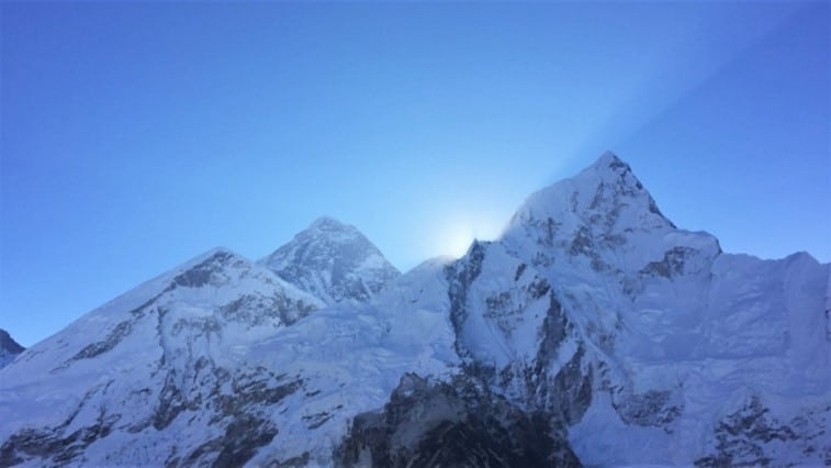 A view of the sun rising from behind Mount Everest
